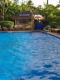 Hotel pool. A hotel pool with sparkling blue water and pool chairs for sunbathers Royalty Free Stock Photos
