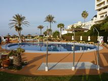 Hotel pool in Spain with palm trees royalty free stock image