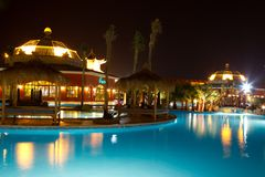 Hotel pool at night. Outdoor swimming pool and poolside facilities at night in an Egyptian hotel with golden lights reflecting on blue water Royalty Free Stock Images