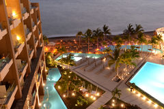Hotel pool at night. Aerial view of hotel pool in seaside resort illuminated at night Royalty Free Stock Photos