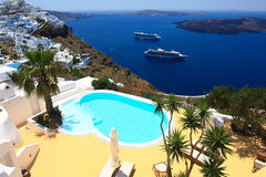 Hotel pool overlooking caldera of santorini. Small pool of a private hotel perched on the cliffs of the island of santorini overlooking the volcano and cruise Royalty Free Stock Photos