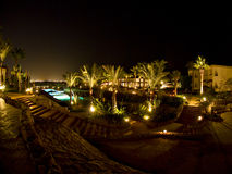 Hotel pool and palm trees. The courtyard of a hotel with a pool and palm trees at night Stock Photos