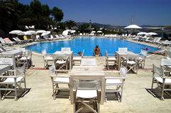 Hotel pool and patio. A view of a beautiful pool and patio surrounded by white tables, chairs and loungers, found at a hotel in Bodrum, Turkey Royalty Free Stock Images