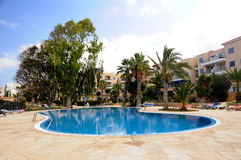Hotel pool - in the shade of eucalyptus. Hotel pool Paphos - tree shadow on the surface of the pool Royalty Free Stock Image