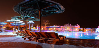 Hotel pool. A hotel pool and sun loungers at night Stock Photos