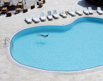 Hotel pool. Top view with young man swimming at the middle Royalty Free Stock Photography