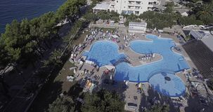 Hotel pool in Tucepi aerial view. TUCEPI, CROATIA - September 22, 2016 Aerial view of the Neptun hotel pool on a sunny day, paning to the sea stock footage