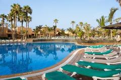 Hotel Poolside-leeres Rattan Sunbeds nahe Schwimmen-Abstimmung mit ruhigem blauem Crystal Clear Water And Concrete, der Boden pfl lizenzfreie stockfotografie