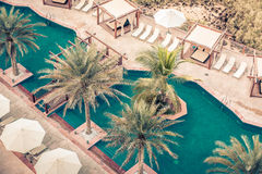 Hotel Poolside with Parasols and Palms Royalty Free Stock Images