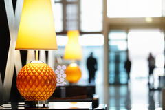 Hotel reception area. Reception area in luxury hotel close up on lamp with people traveling in and out the front entrance Stock Photography