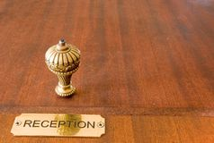 Hotel reception bell. An old, decorative hotel service bell, with a golden reception plate, brown table top Stock Photos