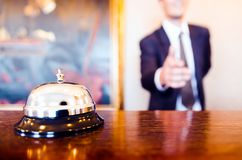 Hotel reception bell receptionist greeting handshake. Hotel reception bell and receptionist greeting handshake Royalty Free Stock Photo