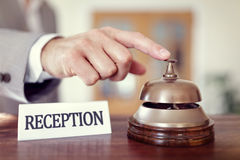 Hotel reception service bell. Businessman ringing a hotel reception service bell to attract attention Stock Photo