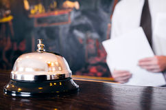 Hotel reception service bell with concierge holding a file. In background Royalty Free Stock Photo
