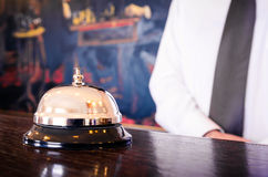 Hotel reception service bell with concierge. Welcoming in the background Royalty Free Stock Photography