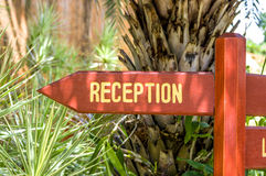 Hotel reception sign. Wooden arrow pointing sign indicating direction of reception of hotel resort Stock Photos