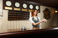 Hotel receptionist and counter desk with bell Royalty Free Stock Image