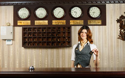 Hotel receptionist at counter desk with card Stock Image