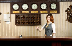 Hotel receptionist at counter desk with keys Stock Image