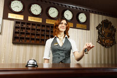 Hotel receptionist at counter desk with keys Royalty Free Stock Photography