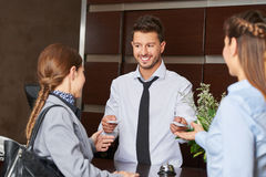 Hotel receptionist giving out key cards Royalty Free Stock Photo