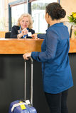 Hotel receptionist handing over a room key card at check in Royalty Free Stock Photography