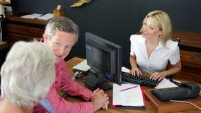 Hotel Receptionist Helping Senior Couple To Check In stock video footage