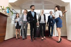 Hotel Receptionist Meeting Business People Group In Lobby. Guests Arrive Royalty Free Stock Photo