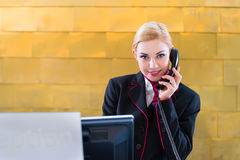 Hotel receptionist with phone on front desk Royalty Free Stock Photo