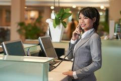 Hotel receptionist. Smiling Vietnamese hotel receptionist talking on phone stock images