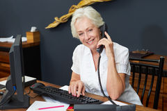 Hotel Receptionist Using Computer And Phone Stock Photo