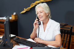 Hotel Receptionist Using Computer And Phone Royalty Free Stock Photos