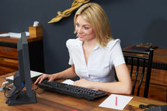 Hotel Receptionist Working At Computer Stock Photos