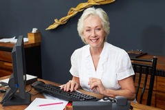 Hotel Receptionist Working At Computer Royalty Free Stock Photos