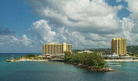 Hotel resort with beach surrounded by ocean and sky with clouds Stock Images