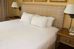 Hotel Resort Bed And White Linen. Pure white pillows and linen bed sheets of hotel resort Royalty Free Stock Image