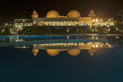 Hotel resort at night with reflection in swimming pool Royalty Free Stock Photos