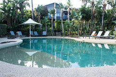 Hotel resort swimming pool surrounded by tropical garden Royalty Free Stock Image
