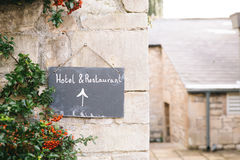 Hotel and Restaurant Signage on Brown Concrete Wall Royalty Free Stock Photos