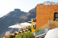 Hotel and restoraunt terasse with famous Skaros rock on the back. Hotel and restoraunt terasse with famous Skaros rock and Oia village on the background Royalty Free Stock Images