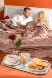 Hotel romântico de encontro do pequeno almoço da cama dos pares felizes Imagem de Stock Royalty Free