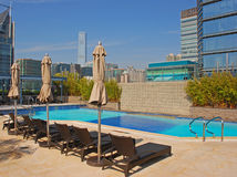 Hotel Rooftop Swimming Pool with deckchair & Buildings Stock Photo