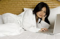Hotel Room #1. An attractive asian woman lies on the bed in a robe with laptop and phone Stock Photos