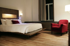 Hotel room. Nice hotel room with red sofa and wooden floor stock image