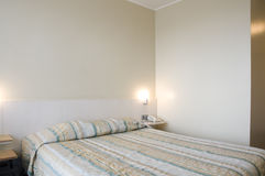 Hotel room. Hotel economy room with bed, telephone and emply walls Royalty Free Stock Images