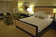 Hotel Room. Interior of hotel room in warm tone. Queen size bed and relax zone Stock Photos