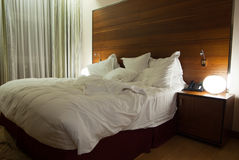 Hotel room. Unmade bed with white duvet Royalty Free Stock Images