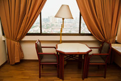 Hotel Room. View of table and chairs with table lamp in a hotel room near window Stock Photography
