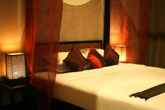 Hotel room. Luxury hotel room, asian style with red pillows and bamboo lamps Stock Photography