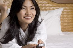 Hotel Room #4. A pretty young woman with remote control on hotel bed - close-up Royalty Free Stock Image